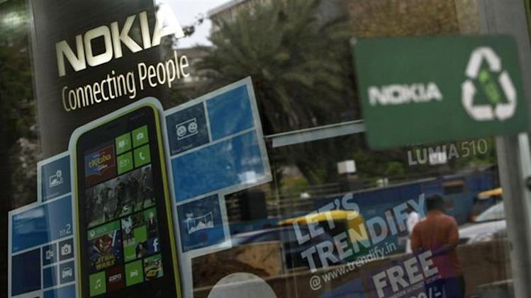 A man is reflected on the glass door of a Nokia showroom in New Delhi March 28, 2013.