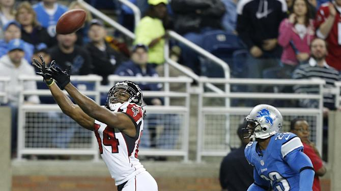 Atlanta Falcons wide receiver Roddy White, defended by Detroit Lions cornerback Chris Houston (23), reaches for the ball on a touchdown reception during the first quarter of an NFL football game at Ford Field in Detroit, Saturday, Dec. 22, 2012. (AP Photo/Rick Osentoski)