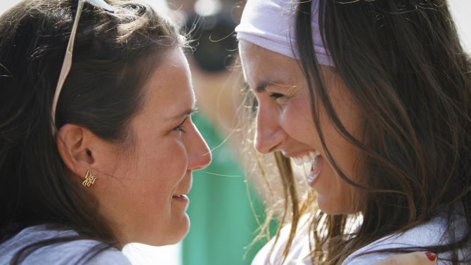Jenn Gibbons, right, is reunited with a supporter after completing a 1,500 mile rowing trip around Lake Michigan to raise money for an organization helping cancer survivors on Tuesday, Aug. 14, 2012 in Chicago. (AP Photo/Sitthixay Ditthavong)