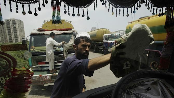 A man cleans the windscreen of an oil tanker used to transport NATO fuel supplies to neighboring Afghanistan, in Karachi, Pakistan, Thursday, May 17, 2012. Pakistan's president announced Thursday that he will attend the upcoming NATO summit in Chicago, accepting an invitation that was given after the country indicated it plans to end its six-month blockade of supplies meant for coalition troops in Afghanistan. (AP Photo/Fareed Khan)