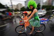 "A woman rides a bike with her daughter during the third ""SkirtBike"" in Bucharest on June 2, 2013. More than 1,500 Romanian women in colourful skirts and high heels cycled through the country's main cities to promote urban biking as a ""stylish and fun"" way of transport"