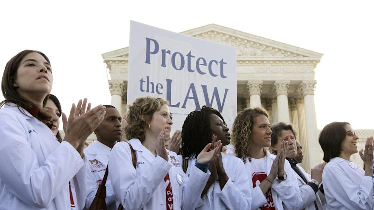Doctors and medical students supporting the health care reform law signed by President Obama gather in front of the Supreme Court in Washington, Monday, March 26, 2012, as the court begins three days of arguments on health care. (AP Photo/Charles Dharapak)