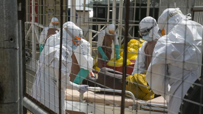 British health workers lift a newly admitted Ebola patient onto a wheeled stretcher in to the Kerry town Ebola treatment centre outside Freetown