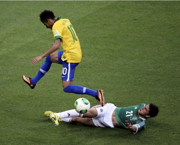 Brazil's Neymar jumps over the challenge of Mexico's Hiram Mier during their Confederations Cup Group A soccer match at the Estadio Castelao in Fortaleza