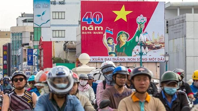 LIN08. Ho Chi Minh (Viet Nam), 18/04/2015.- People ride past a billboard hung at a corner which marks the 40th anniversary of the end of the Vietnam War, in Ho Chi Minh, Vietnam 18 April 2015. Vietnam prepares to celebrate the 40th anniversary of the fall of Saigon, or Ho Chi Minh City's former name. In Ho Chi Minh City, the day will be marked with various official events, including incense ceremonies a special art program and a bicycle race. EFE/EPA/LE QUANG NHAT
