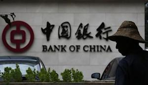 A man is silhouetted in front of a Bank of China's logo at its branch office in Beijing