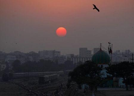 A bird flies over a shrine as the sun sets in Karachi