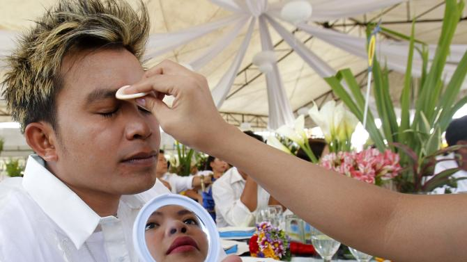 A bride is seen reflected in a mirror as she applies face powder on her groom before a Valentine's Day mass wedding in Marikina City
