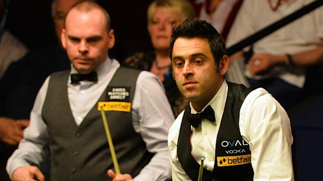 Ronnie O'Sullivan of England (R) plays a shot as Stuart Bingham of England (L) watches during their quarter-final match at the World Championship at The Crucible in Sheffield.