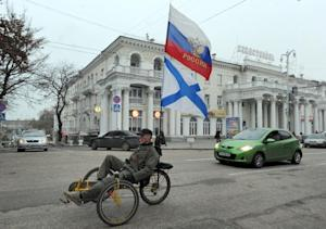 A pro-Russian activist rides a bicycle decorated with …