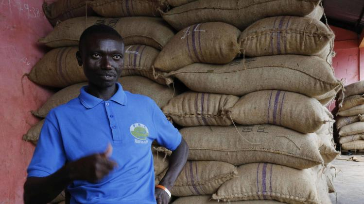 Cocoa farmer Assum gestures at his warehouse in Dabisso