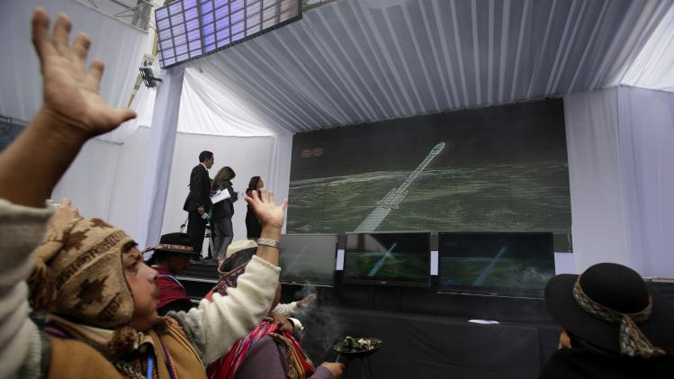 Bolivian indigenous witch doctors watch the launch of the Tupac Katari satellite on a screen in La Paz