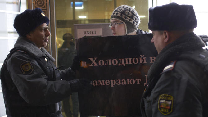"A protester argues with police officers outside the Federation Council on Wednesday, Dec. 26, 2012. Several protesters were detained Wednesday morning outside the upper chamber of Russia's parliament as it prepared to vote on a controversial measure banning Americans from adopting Russian children. The poster held by the protester reads: ""Children get frozen in the Cold War."" (AP Photo/Alexander Zemlianichenko)"