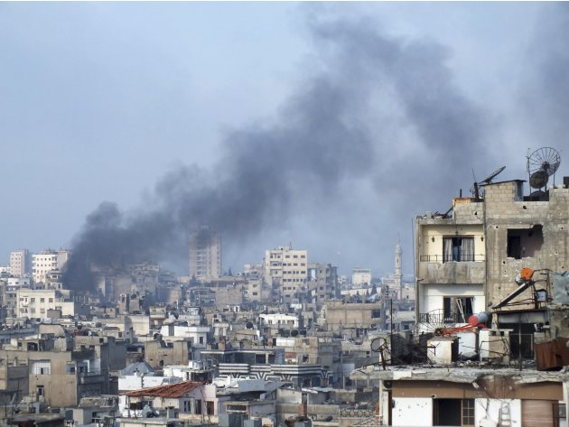 Smoke rises from one of the buildings in the city of Homs