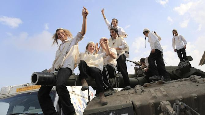 Ultra-Orthodox Jews of the Bratslav Hasidic sect, that gathered to show support for the forces, dance as they celebrate atop of a tank in southern Israel, close to the Israel Gaza Strip Border, Thursday, Nov. 22, 2012. A cease-fire agreement between Israel and the Gaza Strip's Hamas rulers took effect Wednesday night, bringing an end to eight days of the fiercest fighting in years and possibly signaling a new era of relations between the bitter enemies. (AP Photo/Tsafrir Abayov)