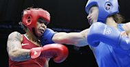 Adriana Araujo of Brazil  (in red) defends against Sofya Ochigava of Russia (in blue) during the women's Lightweight boxing semi-finals of the 2012 London Olympic Games at the ExCel Arena August 8, 2012 in London. Ochigava was awarded a 17-11 points victory.      AFP PHOTO / Jack GUEZ