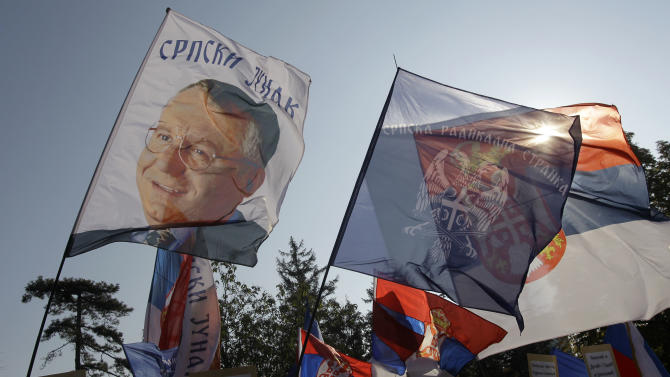 Protesters wave Serbian flags, right, party flag, center and a flag showing Vojislav Seselj, the founder of the ultra-nationalist Serbian Radical Party, currently on trial for alleged war crimes in The Hague war crimes tribunal, during the protest in front of the presidency building in Belgrade, Serbia, Saturday, Nov. 17, 2012. Serbia is furious that the appeals judges at the Hague court on Friday freed Croatian generals Ante Gotovina and Mladen Markac, who previously had been sentenced to lengthy prison terms for crimes against Serbs. (AP Photo/Darko Vojinovic)