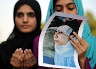 "Islamic Minhaj-ul-Quran Party activists hold a photograph of Malala Yousafzai, shot in the head by the Taliban in retaliation for her campaign for the right to education, as they pray for her recovery in Islamabad. She is making ""slow and steady progress"" in her recovery, the military said Sunday"