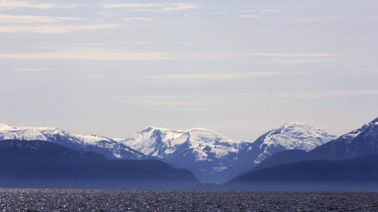 Snow-capped mountains peak out over a cove area favored by fishermen in the Douglas Channel, in northern British Columbia