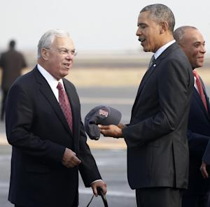 Boston Mayor Thomas Menino, left, gives President Barack Obama a Boston Red Sox cap as he arrives at Boston Logan Airport, Wednesday, Oct. 30, 2013, before going to Faneuil Hall to speak about the federal health care law. Massachusetts Mayor Deval Patrick is at right. (AP Photo/Charles Dharapak)