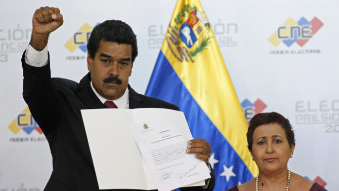 Venezuela's interim President Nicolas Maduro raises his fist as he holds up the official certificate declaring him winner of the presidential election at the Electoral Council in Caracas, Venezuela, Monday, April 15, 2013. Venezuela's government-friendly electoral council has quickly certified the razor-thin presidential victory of Hugo Chavez' hand-picked successor. Nicolas Maduro was elected by a margin of 50.8 percent to 49 percent over challenger Henrique Capriles. At right is Tibisay Lucena, the head of the electoral commission.(AP Photo/Ariana Cubillos)
