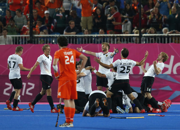 Netherlands' Verga  reacts as Germany's team players celebrate winning during their men's gold medal hockey match at Riverbank Arena at London 2012 Olympic Games