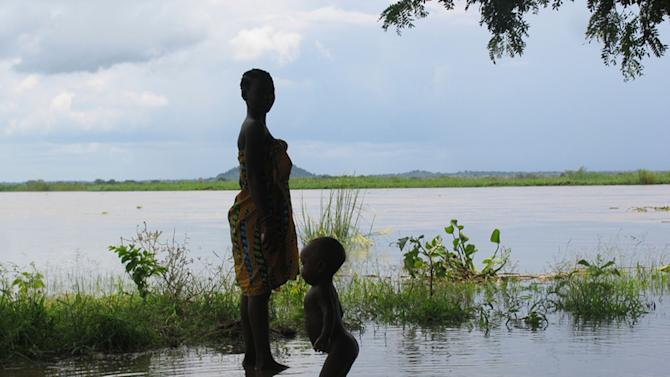 FILE - In this Jan. 9, 2008, file photo provided by UNICEF a woman and child wade in flood waters in Mutarara, Mozambique in the Tete district. Thousands of people who lost their homes in floods last year are at risk again as the rising Zambezi river waters threaten their resettlement camps. Top climate scientists are gathering in Japan to finish up a report on the impact of global warming. And they say if you think climate change is only faced by some far-off polar bear decades from now, well, you're mistaken. They say the dangers of a warming Earth are immediate and human. (AP Photo/Theirry Delvigne-Jean UNICEF)