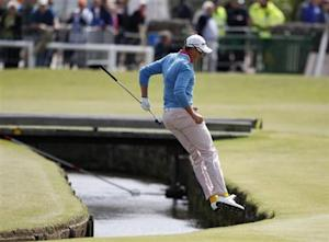 Sweden's Stenson jumps over the Swilcan Burn after chipping onto the first green during the final round of the British Open golf championship on the Old Course in St. Andrews
