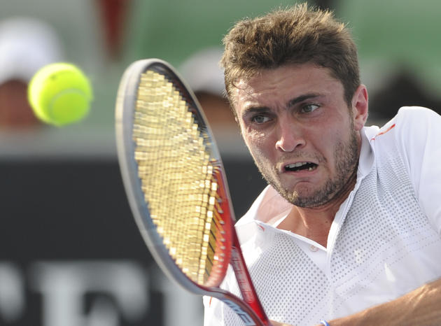 France's Gilles Simon makes a backhand return to Thailand's Danai Udomchoke during their first round match at the Australian Open tennis championship, in Melbourne, Australia, Tuesday, Jan. 17, 2012.