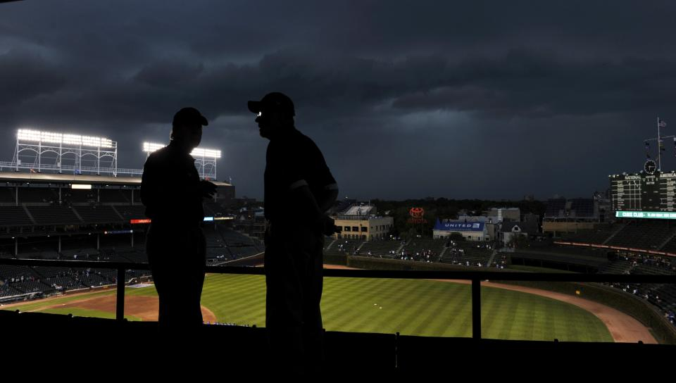 Storm clouds move over Wrigley Field as ushers look at the empty stands during a delay to the start of a baseball game between the Pittsburgh Pirates and Chicago Cubs, Monday, Sept. 17, 2012, in Chicago. (AP Photo/Jim Prisching)