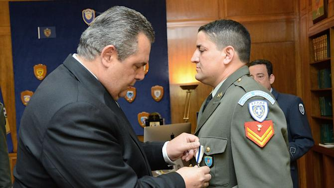 In this photo released by Greek Defense Ministry  on April 27, 2015, Defense Minister Panos Kammenos, left, awards Army Sgt. Antonis Deligiorgis, the Cross of Excellency for his role in rescuing passengers on a ship carrying migrants on the island of Rhodes, at a ceremony in Athens on April 27, 2015. Deligiogis was photographed assisting Eritrean asylum seeker Wegasi Nebiat, in an image that was on front pages of leading world newspapers the following day. Three people died in the shipwreck, while 90 others from Syria and Eritrea were rescued. (Greek Defense Ministry via AP)