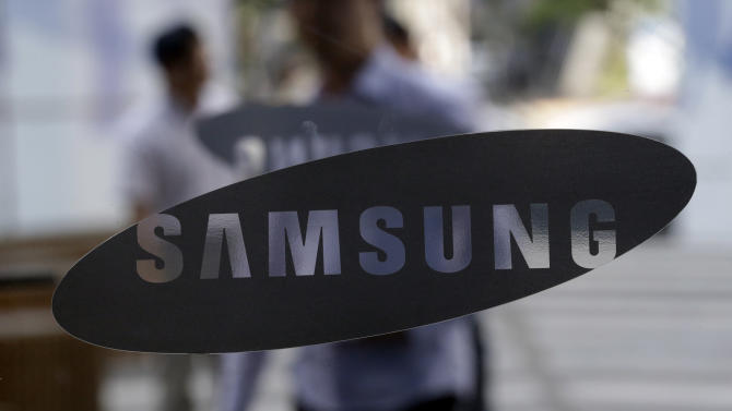 People walk by the entrance to the Samsung Electronics Co. showroom at its headquarters in Seoul, South Korea, Friday, Aug. 31, 2012. The Tokyo District Court on Friday dismissed Apple Inc.'s claim that Samsung had infringed on its patent - the latest ruling in the global legal battle over smartphones that pits the two technology titans against each other. (AP Photo/Lee Jin-man)
