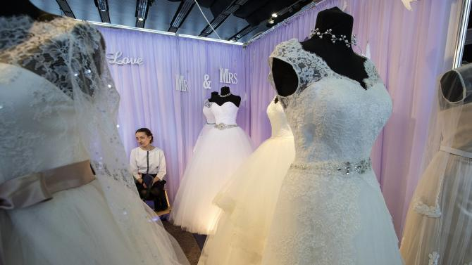 "An employee sits near wedding dresses during the 4th International exhibition ""My wedding"" in Minsk"