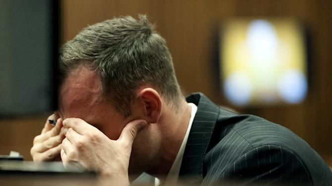 Oscar Pistorius, reacts in the dock during cross examination of a witness in court in Pretoria, South Africa, Tuesday, March 18, 2014. Pistorius is on trial for the murder of his girlfriend Reeva Steenkamp on Valentine's Day, 2013. (AP Photo/Brendan Croft, Pool)