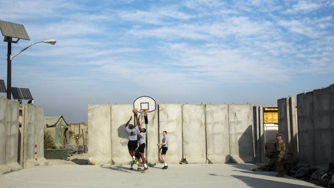 U.S. soldiers play basketball on an outdoor court surrounded by concrete blast walls at Forward Operating Base Fenty in Nangarhar province