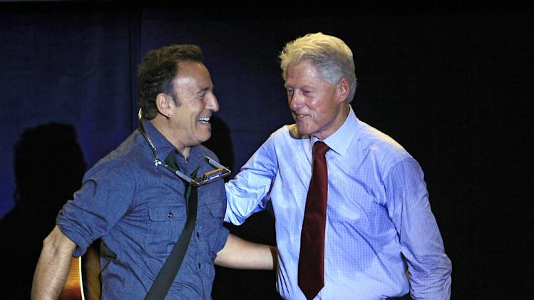 Former President Bill Clinton greets singer/songwriter Bruce Springsteen at a campaign event for President Barack Obama, Thursday, Oct. 18, 2012, in Parma, Ohio. (AP Photo/Tony Dejak)