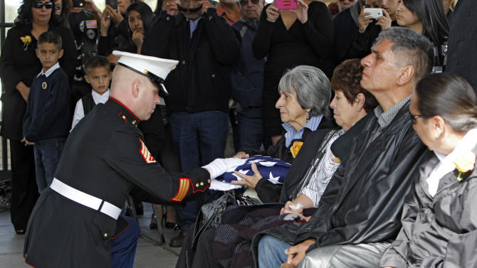 Delouise Guerra the sister of Marine  PFC James Jacques is presented the flag that draped his casket at Fort Logan National Cemetery in Denver on Tuesday, Oct. 9, 2012. The Jacques funeral was held 37 years after he was killed during the rescue of the crew of an American cargo ship seized by Cambodia in May of 1975. His remains were identifies in August 2012. (AP Photo/Ed Andrieski)