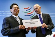 Laos' Industry and Commerce Minister Nam Viyaketh (L) is handed a placard with his country's name by World Trade Organization (WTO) director general Pascal Lamy during a signing ceremony which confirmed Laos as a new member of the international organisation