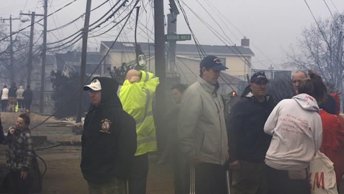 People assess damage caused by a fire at Breezy Point in the New York City borough of Queens Tuesday, Oct. 30, 2012. The fire destroyed between 80 and 100 houses Monday night in an area flooded by the superstorm that began sweeping through earlier. (AP Photo/Frank Franklin II)