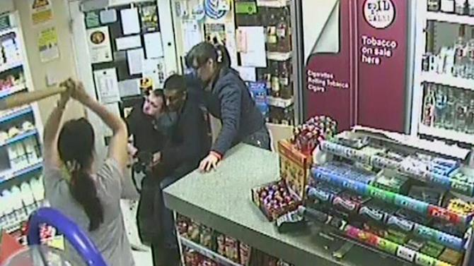 Ex-juvenile offender Shaun Andrew McKerry, dubbed Boomerang Boy in his youth, is leapt on by shop-owner Sab Dhillon and his wife Sam (left, holding a baseball bat) after waving an axe and demanding money (Durham Police/PA Wire)