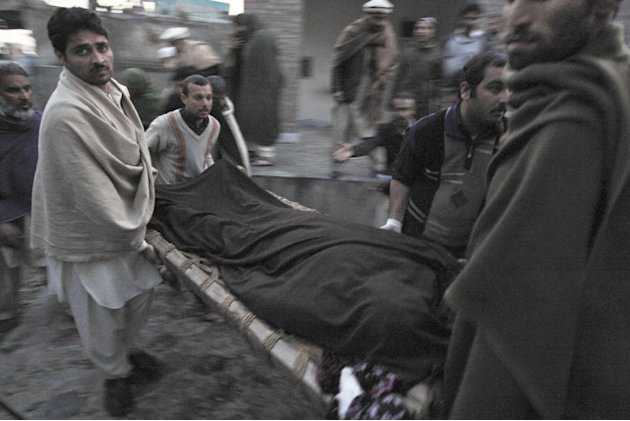 Pakistani men carry the body of a teacher, who was killed by gunmen, from a hospital for burial in Swabi, Pakistan, Tuesday, Jan. 1, 2013. Gunmen in northwest Pakistan killed five female teachers and 