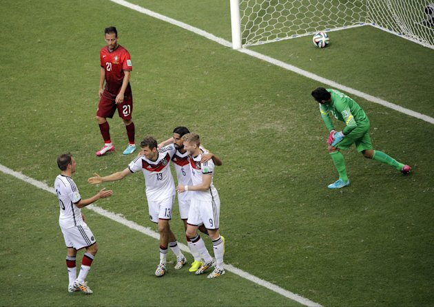 Germany's Thomas Mueller (13) celebrates with teammates after scoring his third goal and Germany's fourth during the group G World Cup soccer match between Germany and Portugal at the Arena Fonte Nova in Salvador, Brazil, Monday, June 16, 2014. (AP Photo/Christophe Ena)
