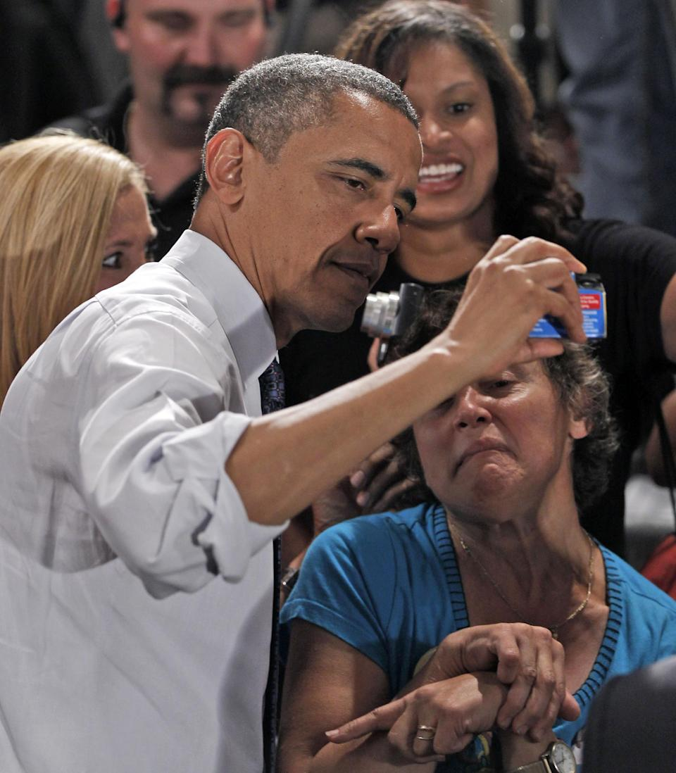 President Barack Obama uses a disposable camera to take a picture with a supporter at a campaign event at the John S. Knight Center, Wednesday, Aug. 1, 2012, in Akron, Ohio. (AP Photo/Pablo Martinez Monsivais)