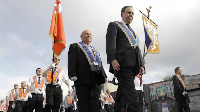 Orange Order members march past the mainly Catholic Ardyone area of North Belfast, Northen Ireland, Thursday, July 12, 2012.  The Twelfth of July is the busiest day of the marching season in Northern Ireland with thousands of Orangemen and women, accompanied by marching bands, taking part in hundreds of parades. The Orange Order holds its main Belfast event, which commemorates King William III's 1690 Battle of the Boyne victory over Catholic King James II. (AP Photo/Peter Morrison)