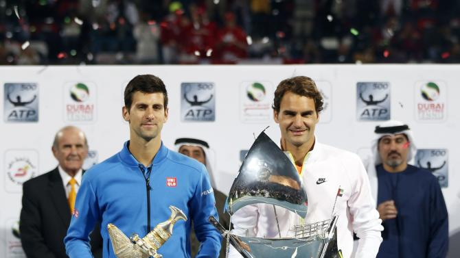 Roger Federer of Switzerland and Novak Djokovic of Serbia pose with their first and second place trophies after their final match at the ATP Championships tennis tournament in Dubai