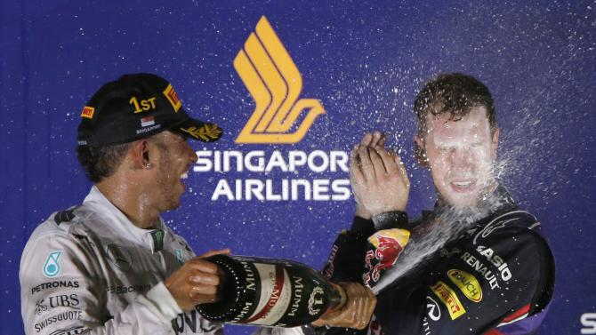 Winner Mercedes Formula One driver Hamilton of Britain sprays champagne over second-placed Red Bull Formula One driver Vettel of Germany during the podium ceremony after the Singapore F1 Grand Prix at the Marina Bay street circuit in Singapore