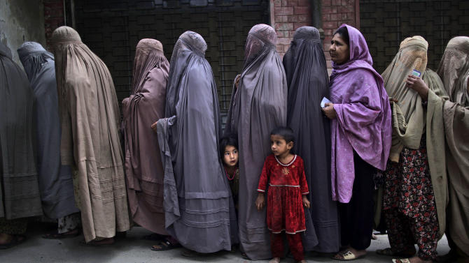 Pakistani women line up to enter a polling station and cast their ballots, on the outskirts of Islamabad, Pakistan, Saturday, May 11, 2013. Pakistanis streamed to the polls Saturday to vote in a historic election pitting a cricket star-turned-politician against an unpopular incumbent and a two-time prime minister, but twin bombings killing nine people and wounding dozens underlined the dangers voters face. (AP Photo/Muhammed Muheisen)