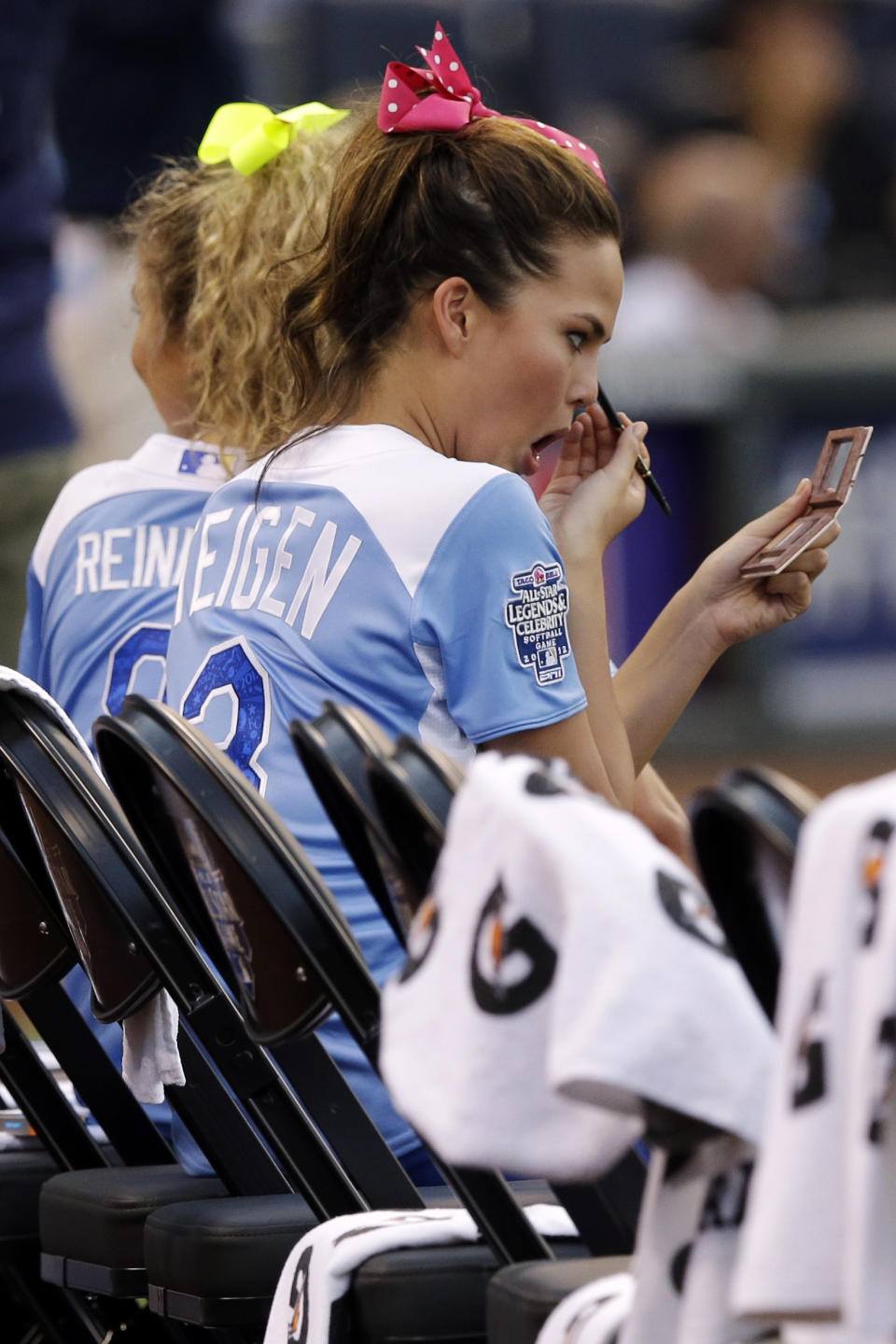 Model Christine Tiegen fixes her makeup during the first inning of the MLB All-Star celebrity softball game, Sunday, July 8, 2012, in Kansas City, Mo. (AP Photo/Charlie Riedel)