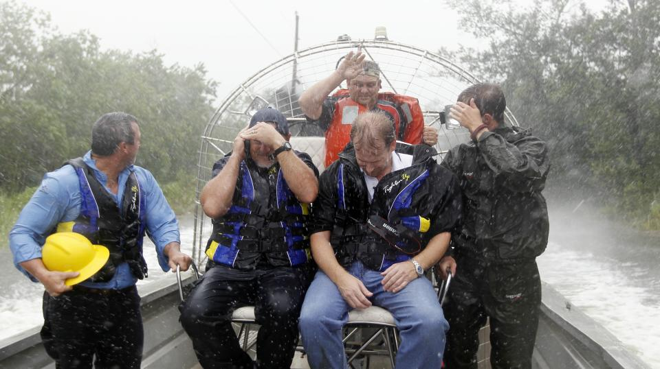 Bay St. Louis, Miss., first responders brave a driving rain storm as they use an airboat to reach a house fire in a flooded subdivision, Tuesday, Aug. 28, 2012. After several attempts to reach the house fire, flooded streets forced the fire fighters to use the airboat.  (AP Photo/Holbrook Mohr)
