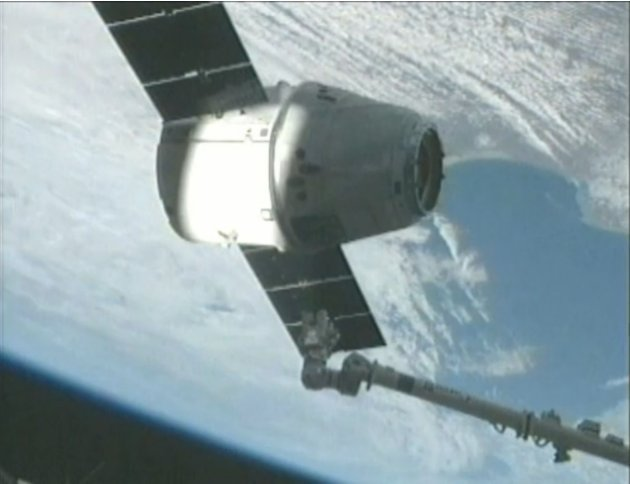 The SpaceX Dragon capsule is captured by the crew of the International Space Station using its robotic arm in this screen capture from NASA handout video